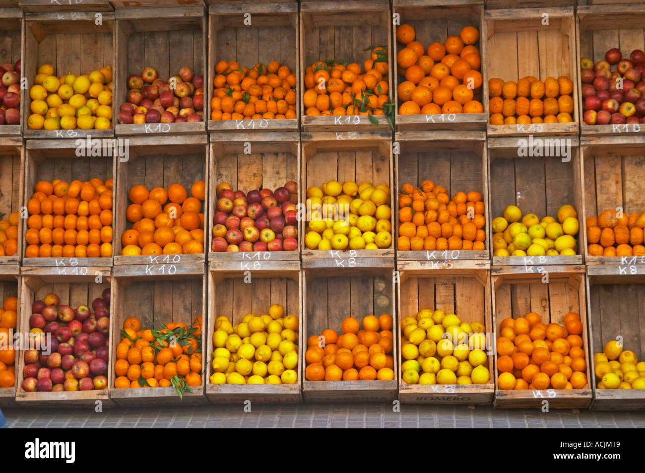 A Fruit And Vegetable Shop Displaying Products In Wooden Crates On The Street Tomatoes Many Types Of Oranges Lemons Apples