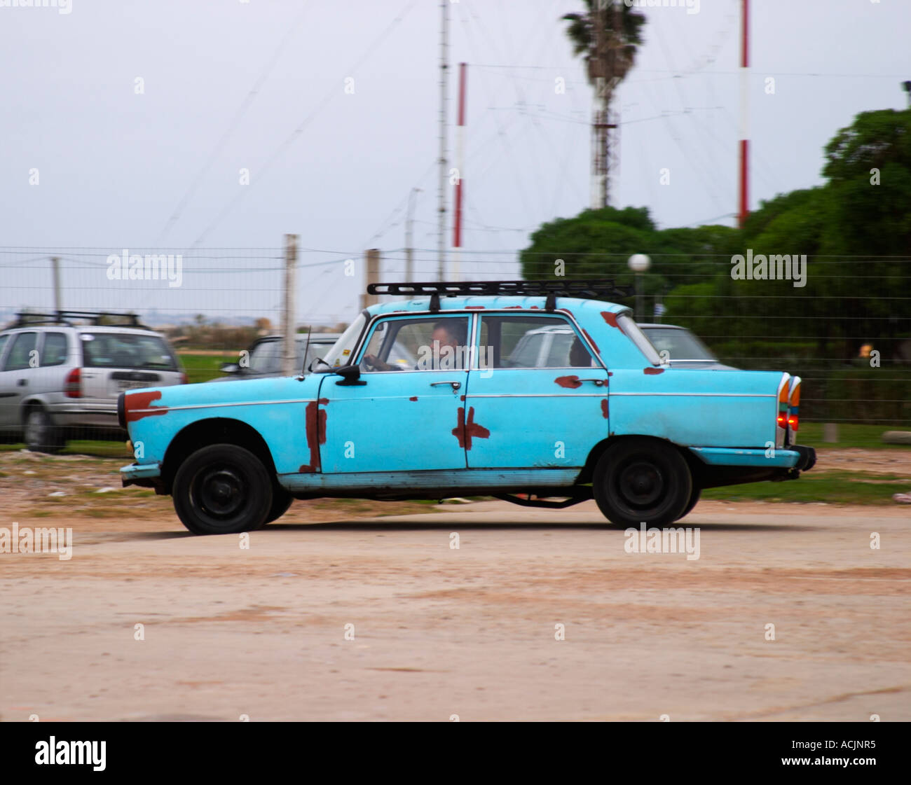 A rusty old 1950s car in blue on a parking lot with a man driving ...