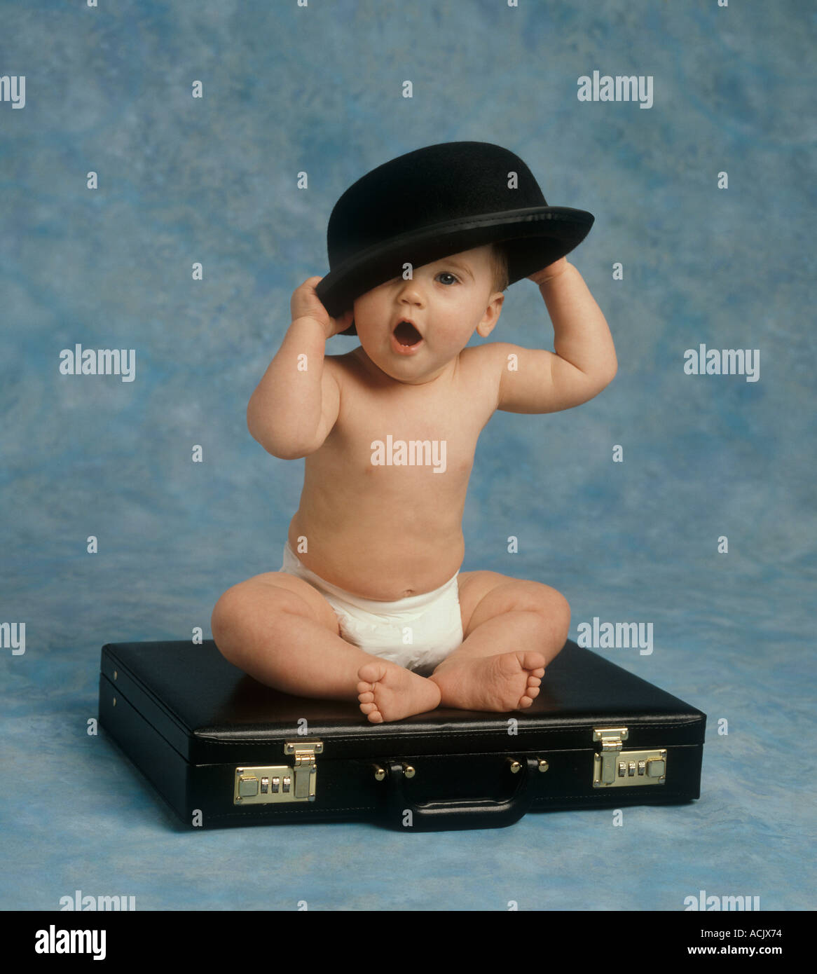 Human baby approx 8 months in nappy sitting on black brief case putting bowler  hat on head shouting a4d27cc324db