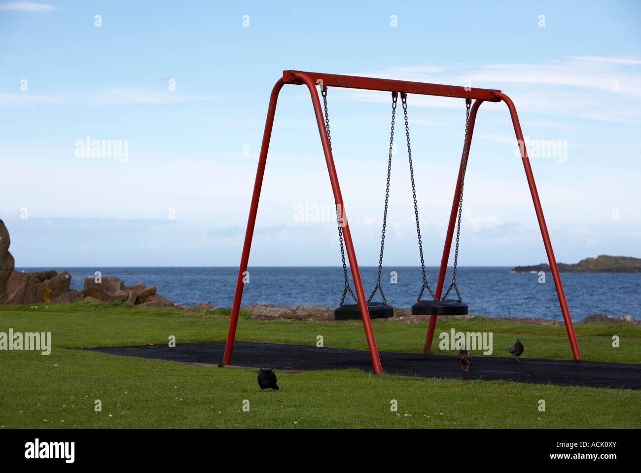 red childrens swings in a playground park on the shore in portrush with pigeons - Stock Image