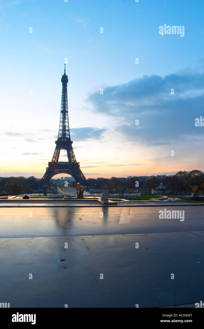 The Eiffel Tower in Paris in early morning dawn with the sun rising on the horizon, pale blue sky some white clouds and the sunlight golden yellow seen from the Place Trocadero square Paris France - Stock Image