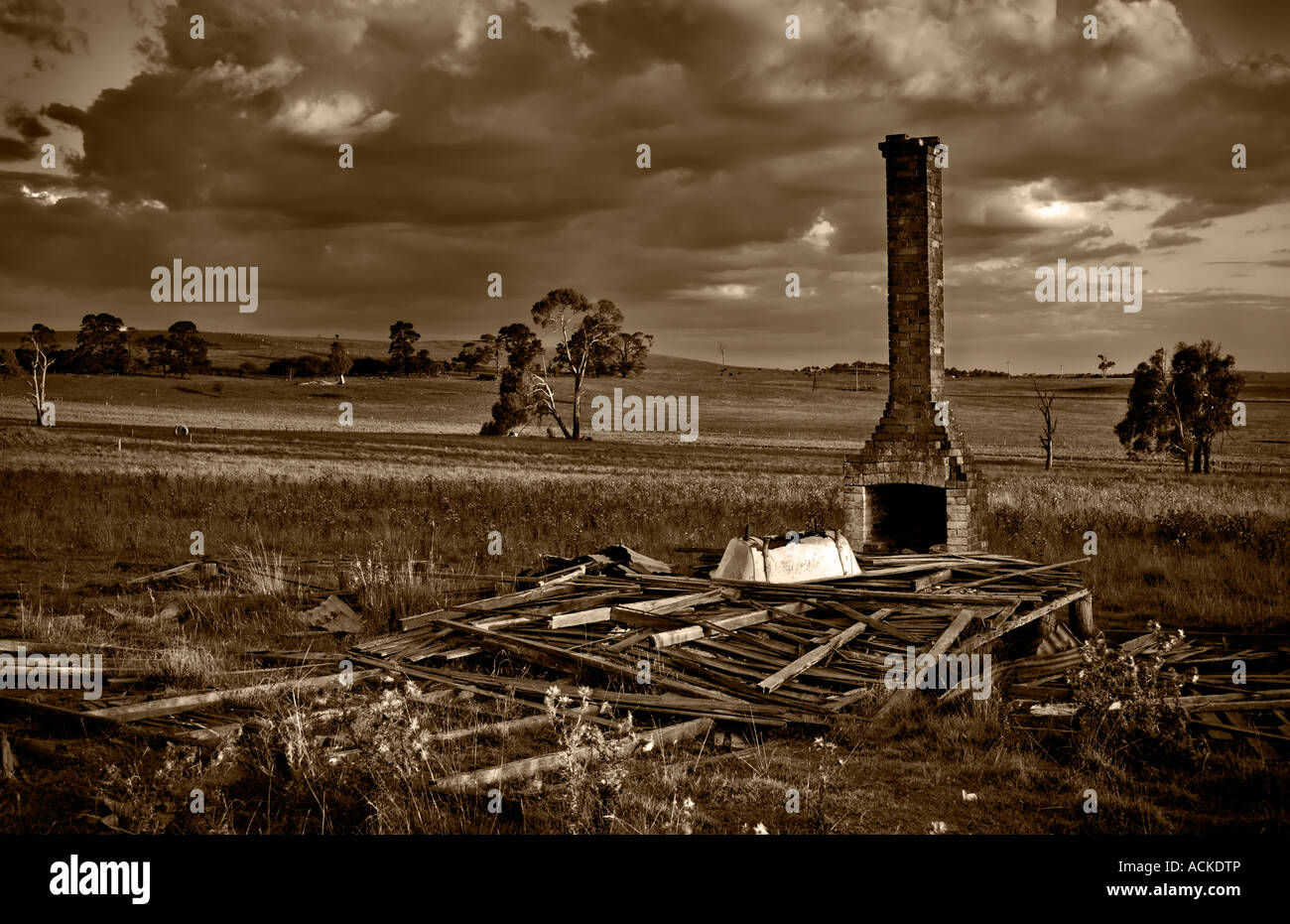 huff n puff sepia image of when a dark storm comes over the fallen down ruins on the farm Stock Photo