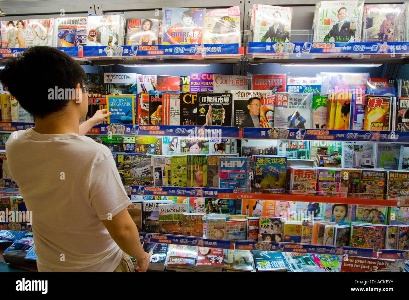 Young Man Picks National Geographic from a Magazine Rack Kowloon Hong Kong - Stock Image