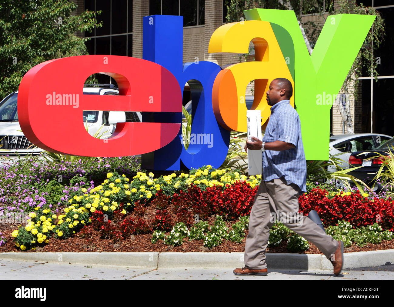 ebay headquarters in San Jose California, an employee carries a computer in front of the ebay logo - Stock Image