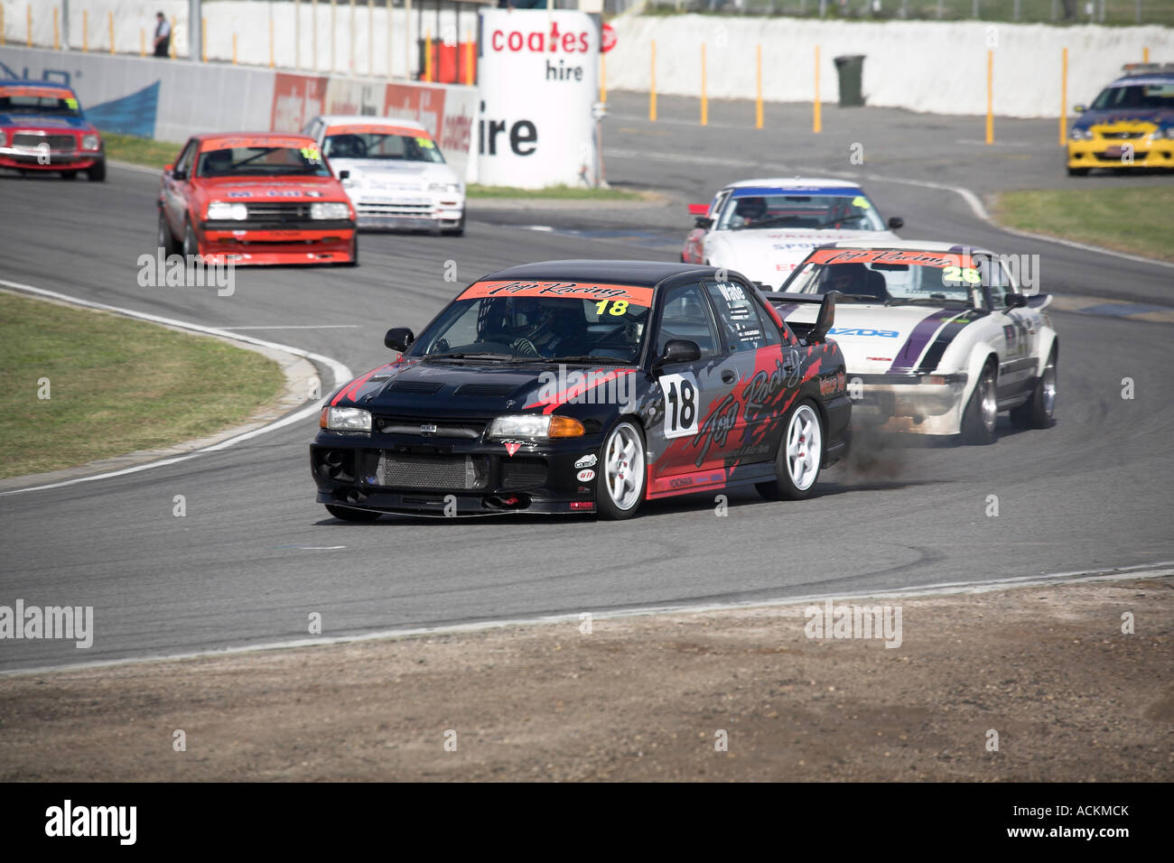 modified Mitsubishi EVO III race car leads the pack into a corner at a circuit racing motorsport event - Stock Image