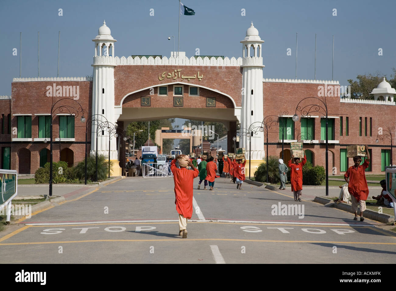 Pakistani porters carry goods through the Wagah Gate, on the border with  India - Stock Image