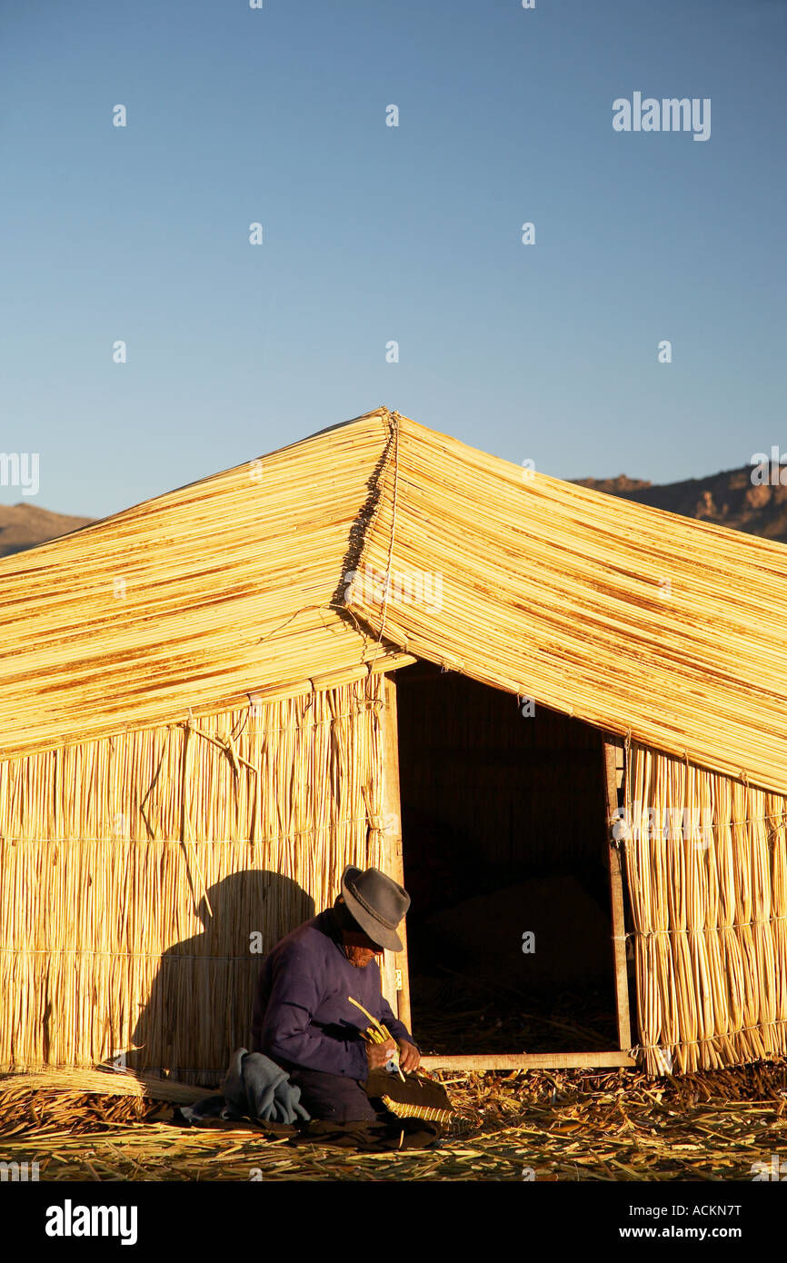 man outside straw house, floating islands, Puno - Stock Image