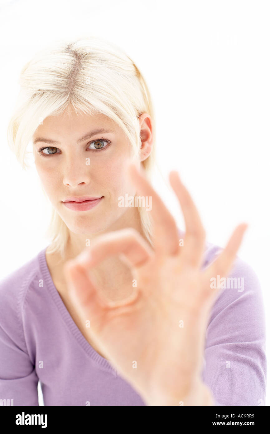 A young woman making a hand signal - Stock Image