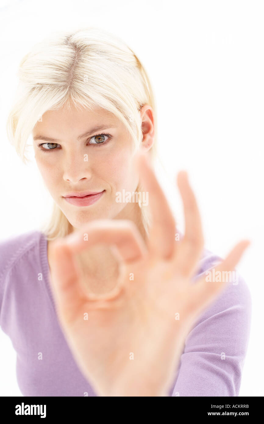 A young woman making a hand signal Stock Photo