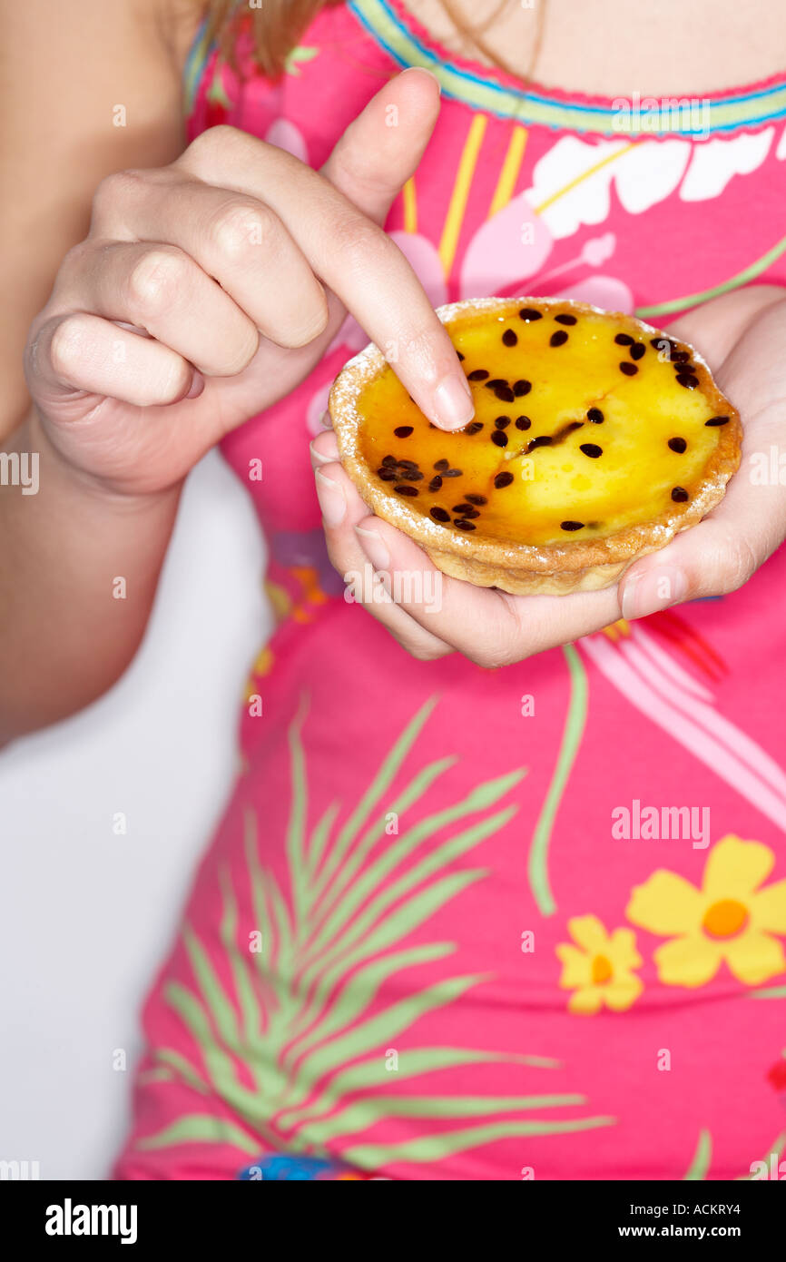 A young woman holding a tart - Stock Image
