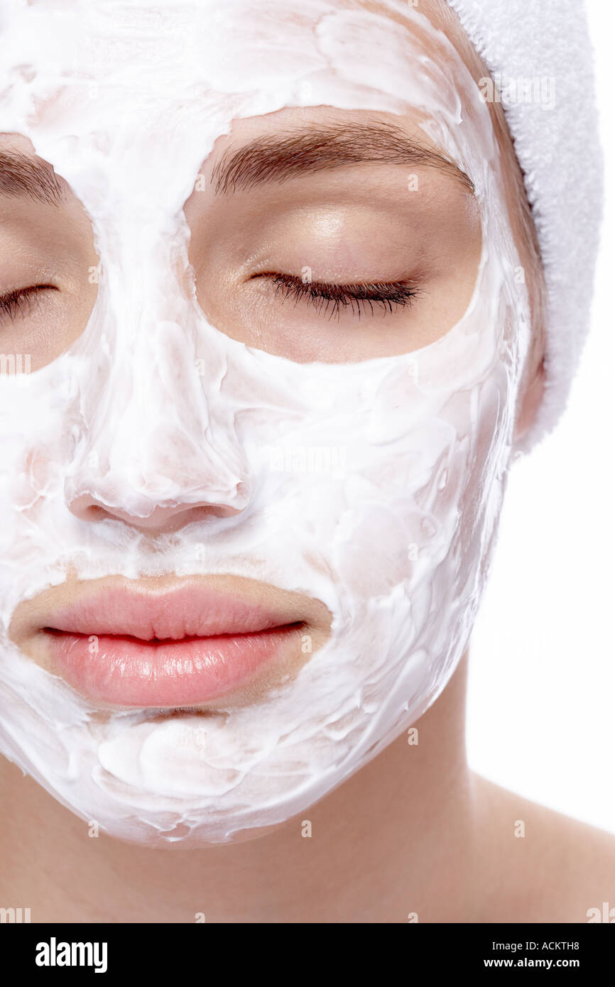 Close up of a young woman with face cream - Stock Image