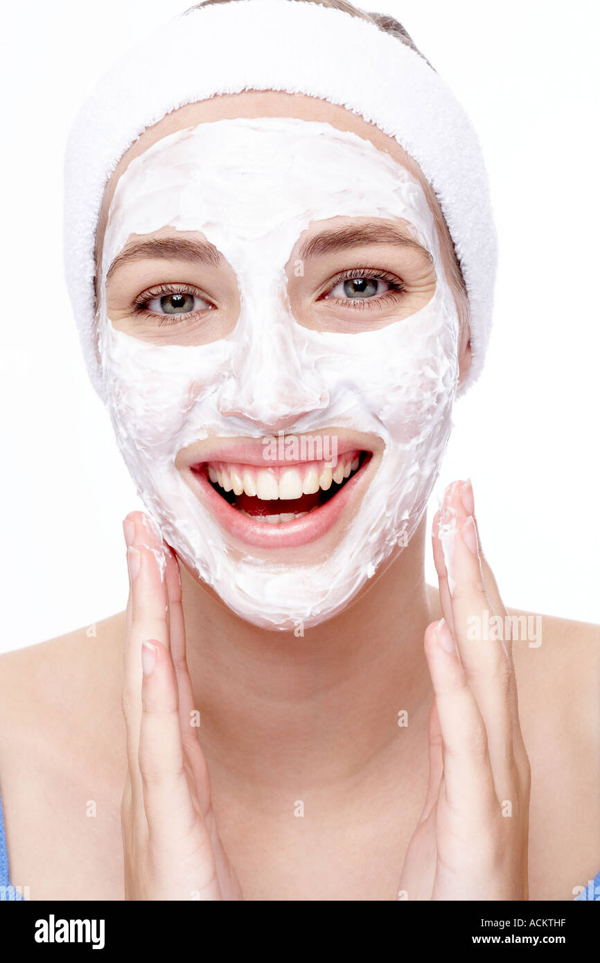 Young woman with cream on face - Stock Image