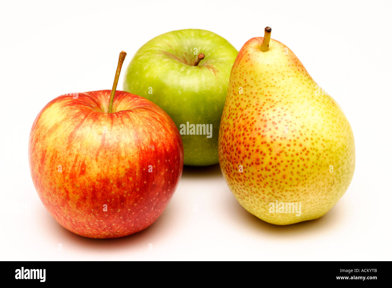 A pear with green and red apples arranged on a white background - Stock Image