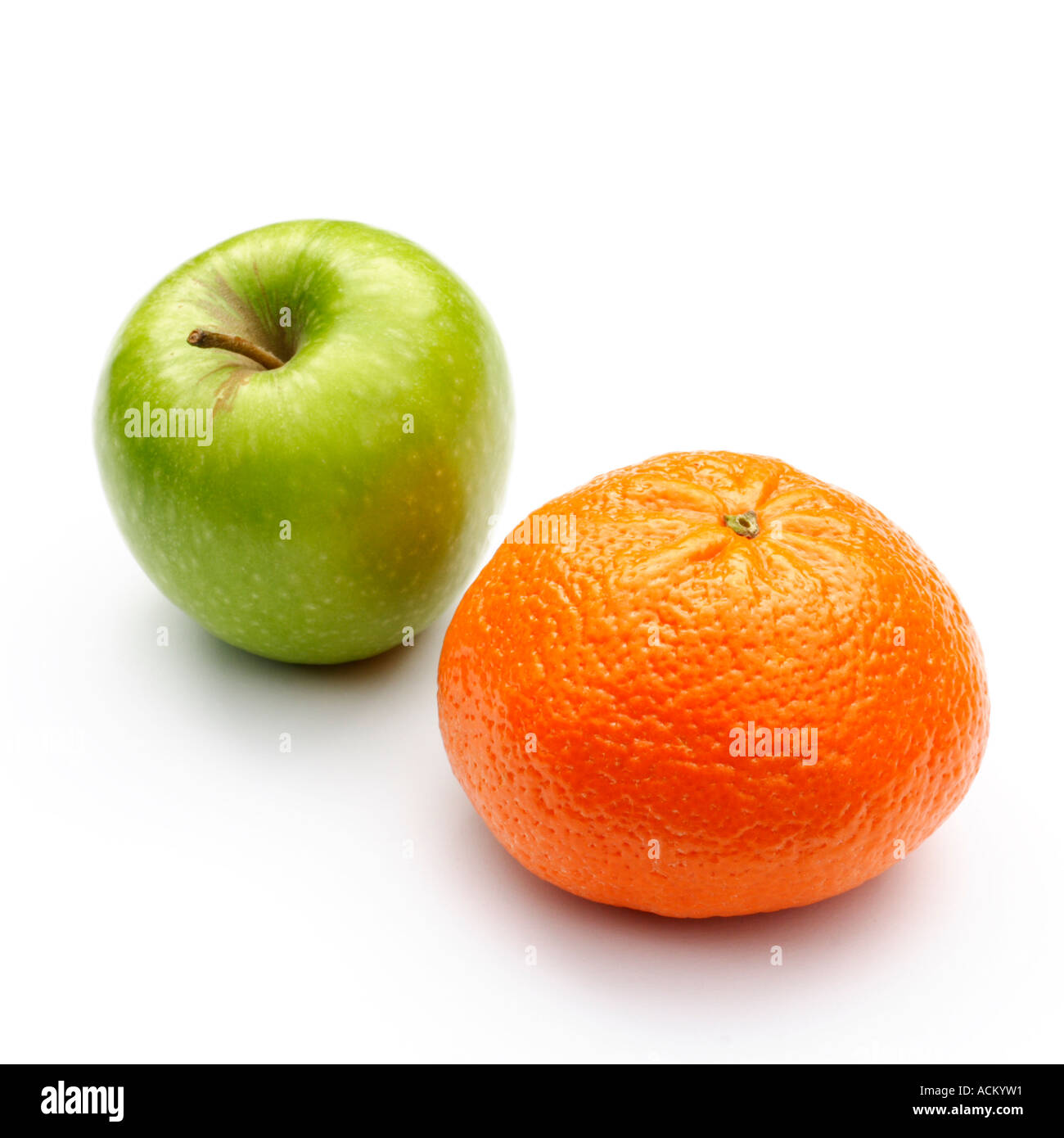 A green apple and a mandarin orange on a white background - Stock Image
