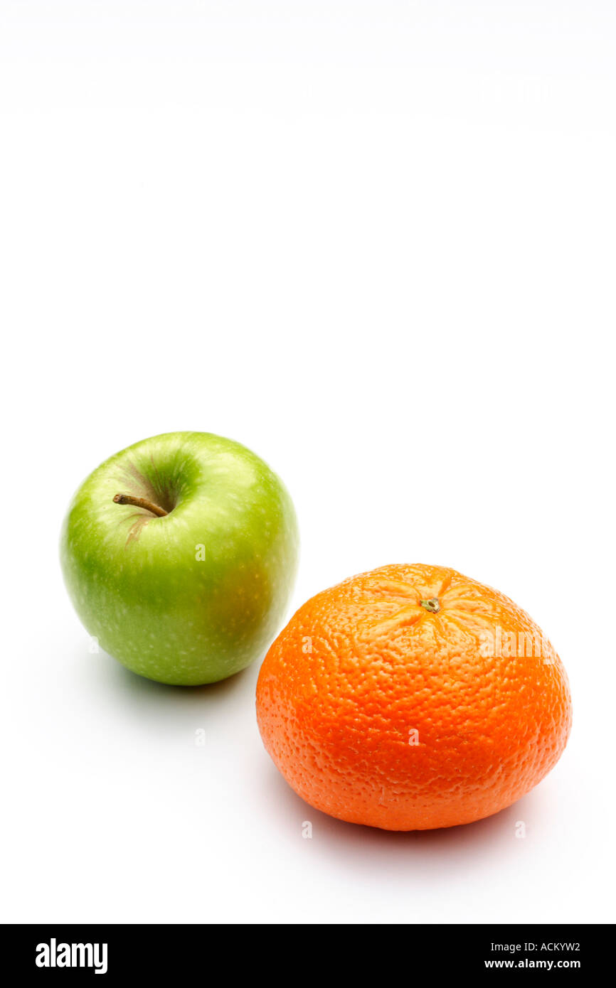 A green apple and a mandarin orange with copy space on a white background - Stock Image