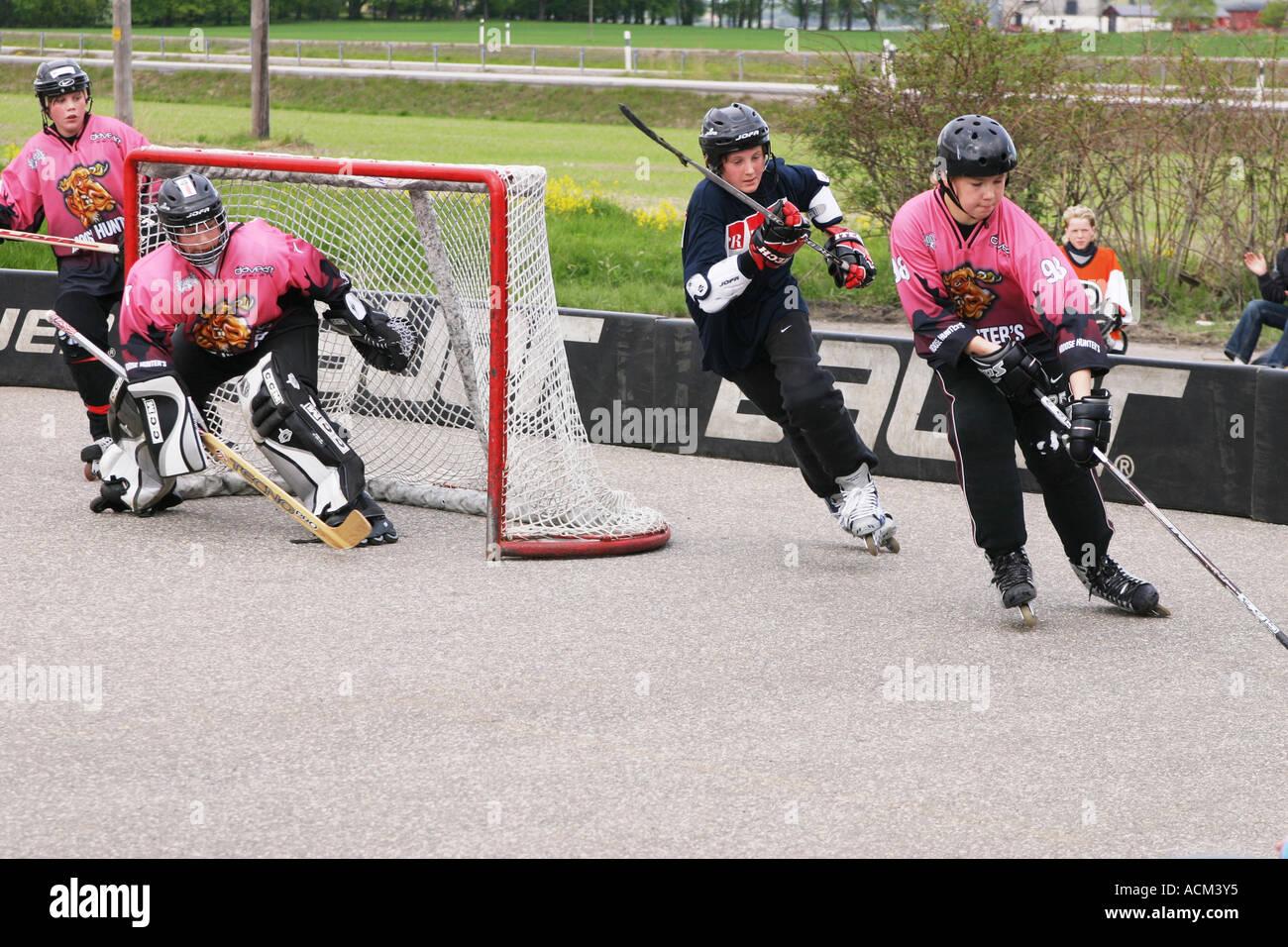 kids playing street hockey on asphalt with inlines hockey
