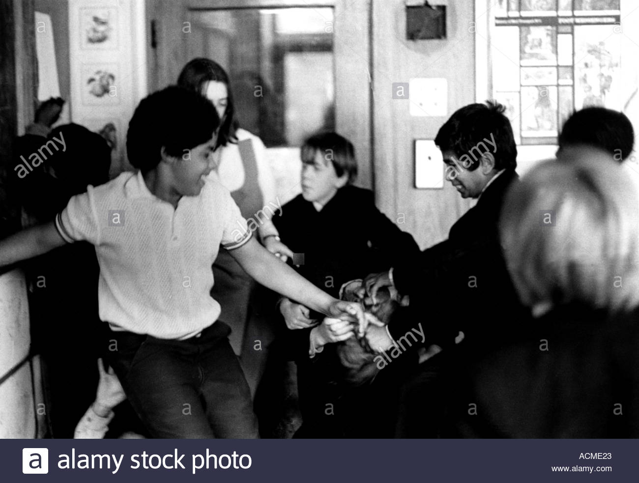 Disruptive class of secondary school children fighting in the classroom - Stock Image