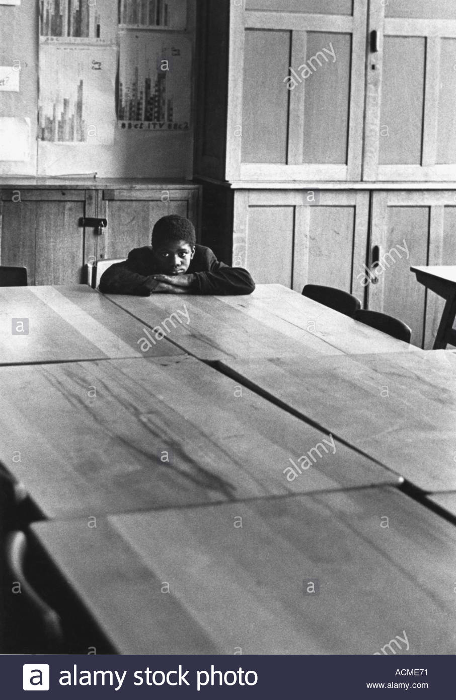 Solitary boy in secondary school classroom - Stock Image