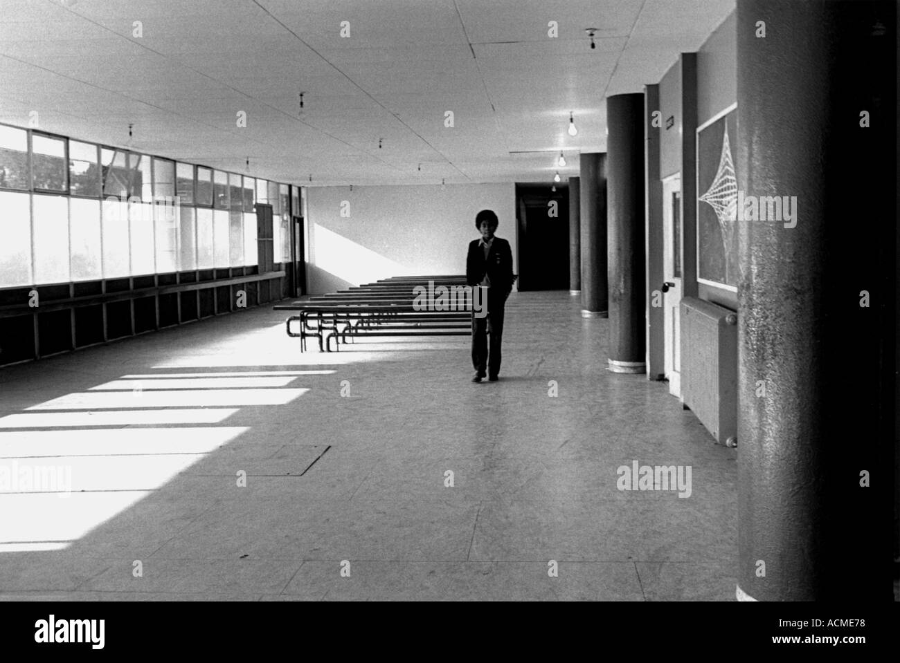 Young boy walking down school hall alone - Stock Image