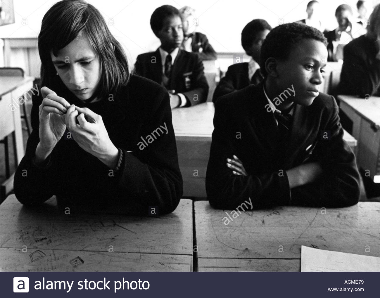 Secondary school pupils sitting in class looking tense but bored - Stock Image