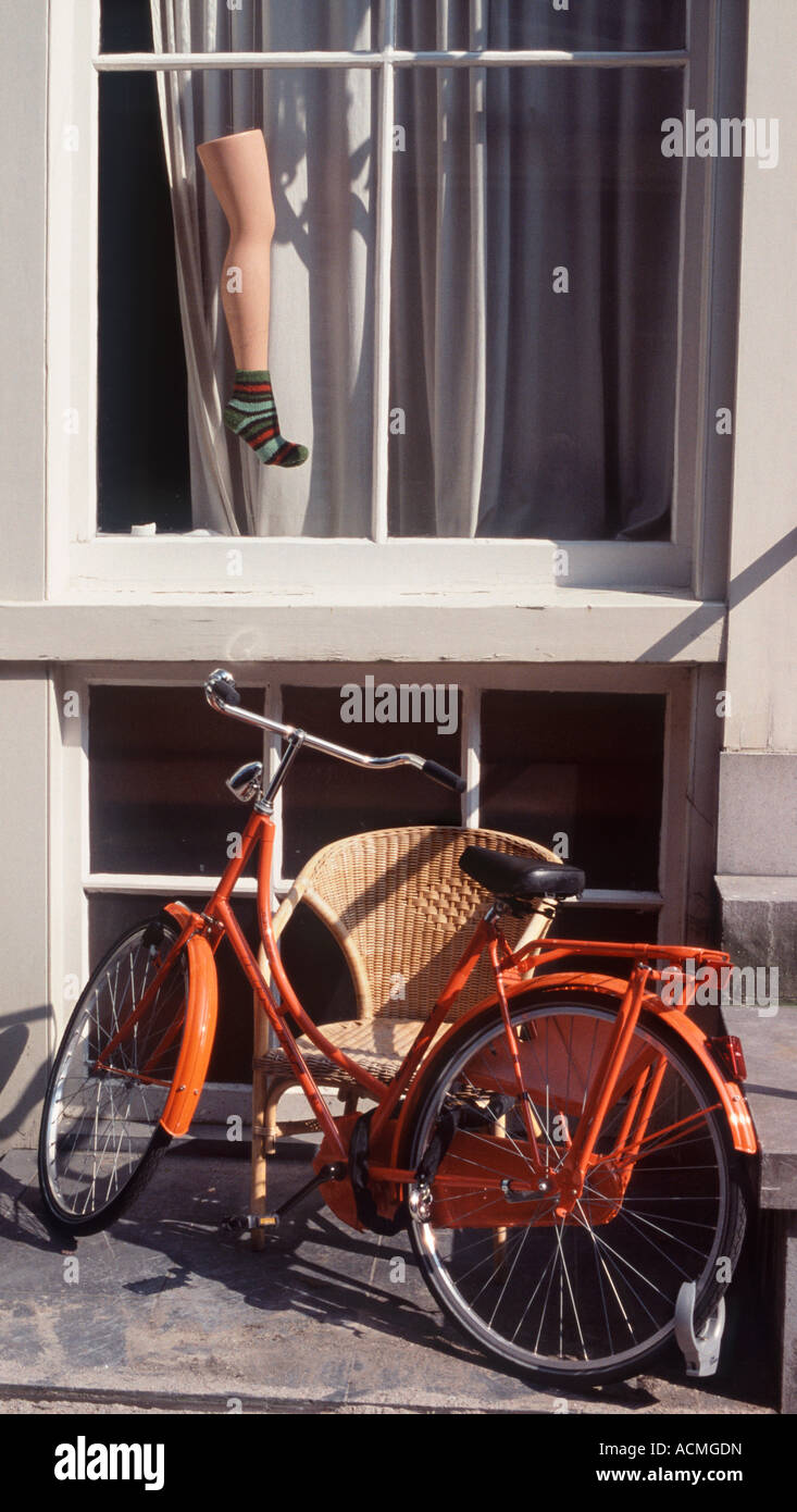 Leg with a Sock: Surrealist window display on house with orange bicycle below, Noorderdwars Straat, Amsterdam, Netherlands - Stock Image