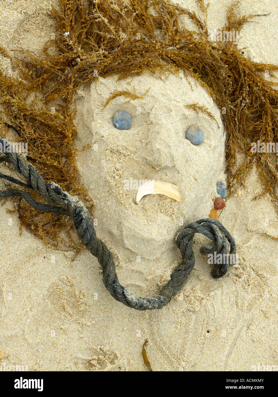 figure of a sad woman face sculptured on Sand with seaweed alga as hair - Stock Image
