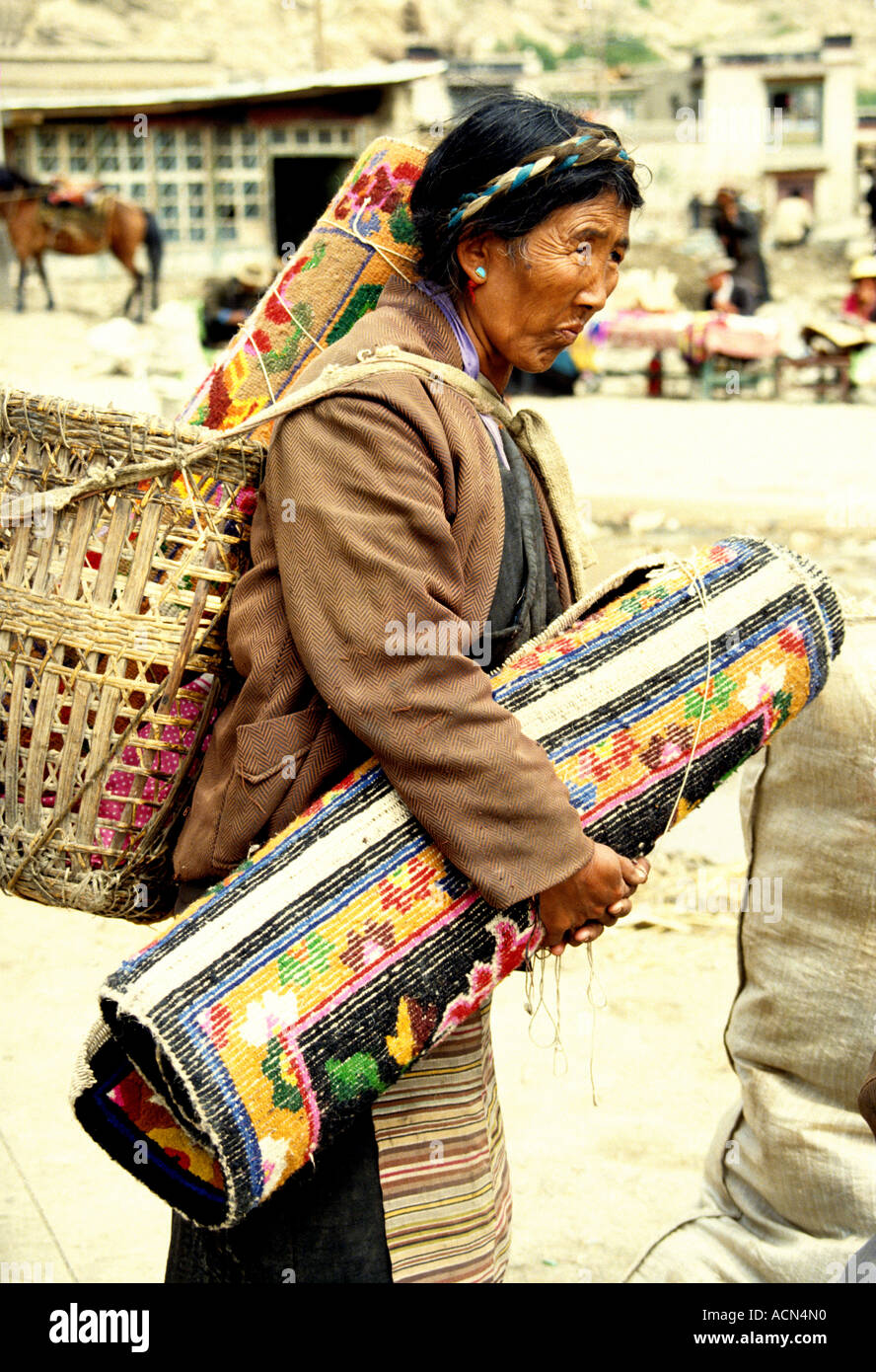 Tibetan  woman selling  locally made colorful  rugs in the market at Gyantse in Tibet - Stock Image