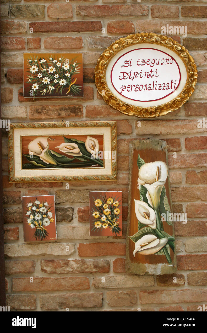 modern paintings hanging on old brick buildings in the hilltown of Sarnano in Le Marche Italy Stock Photo