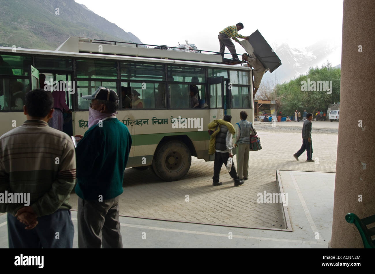 India Himalaya Himachal Pradesh Keylong main bus station view with man climbing to bus top with cupboard on his - Stock Image