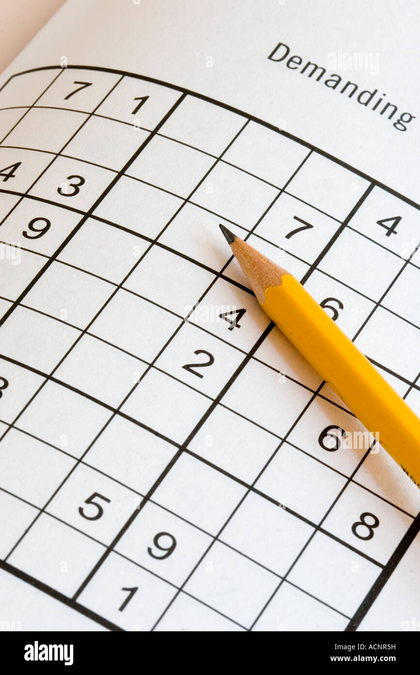 Pencil on a sudoku Japanese number puzzle with the label Demanding indicating how challenging these addictive puzzles - Stock Image