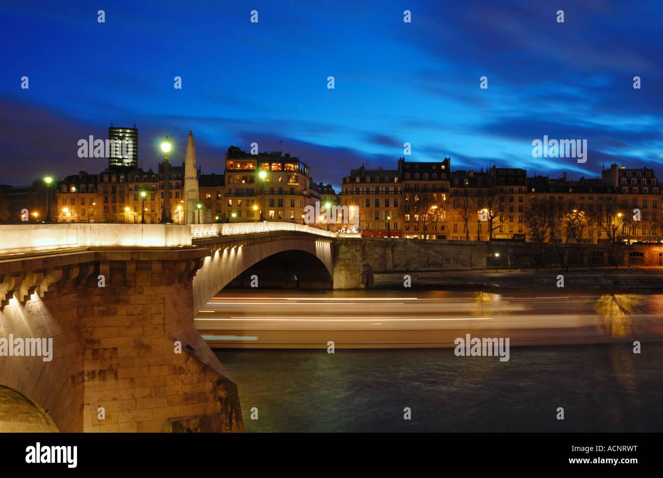 A bateau mouche passing under the Pont De la Tournelle at the blue Hour, Saint-Louis Island, Paris, France - Stock Image