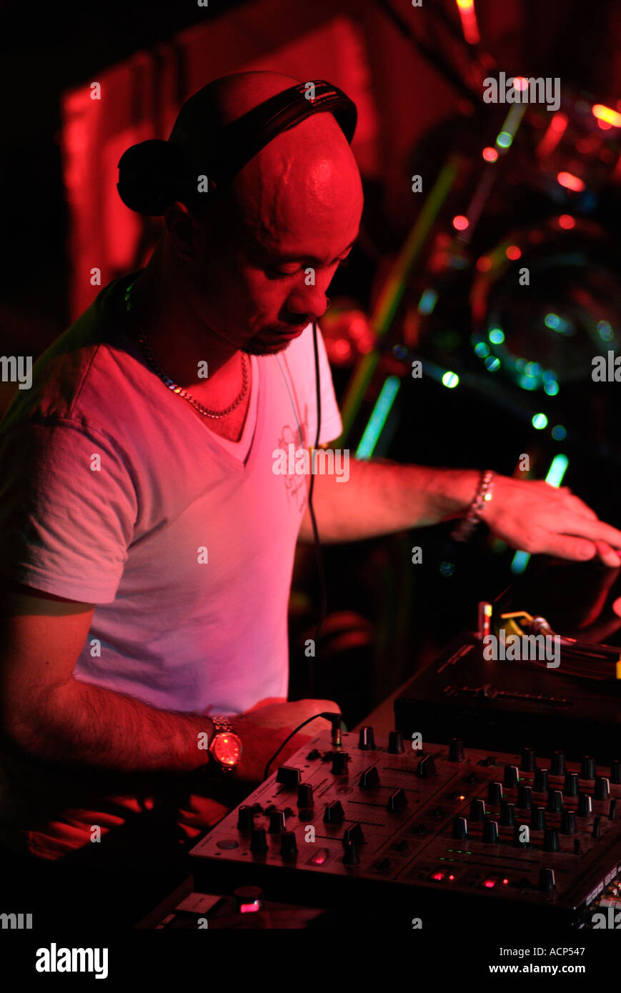 Club DJ Behind the Decks at a Nightclub - Stock Image