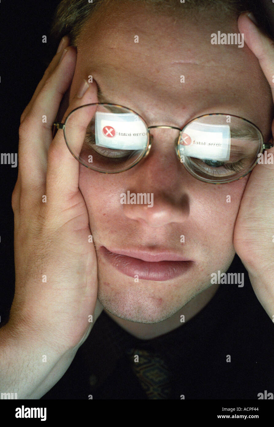 man looking at computer with FATAL ERROR reflected in glasses computer crash idea concept - Stock Image