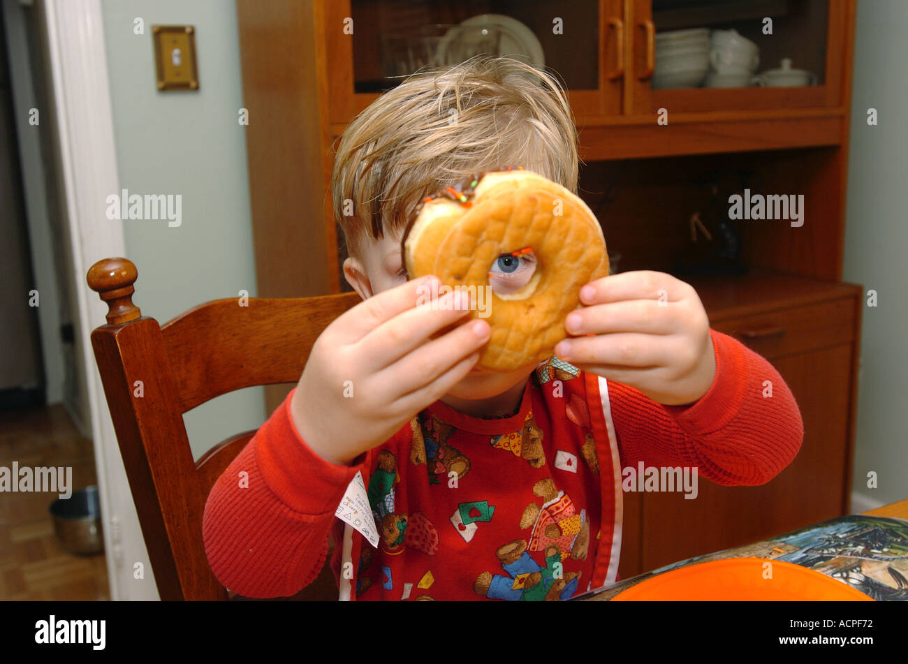 Child Humor small boy looking through a doughnut at a table - Stock Image