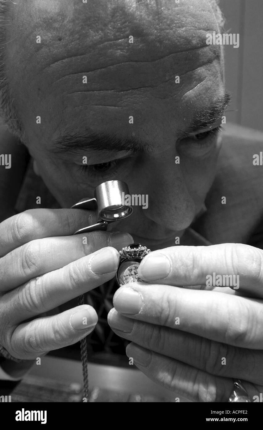 Jeweler examining a ring diamond up close using a magnifying glass - Stock Image