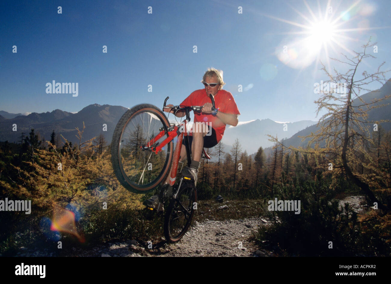 Austria, alps, man mountain biking, low angle view Stock Photo