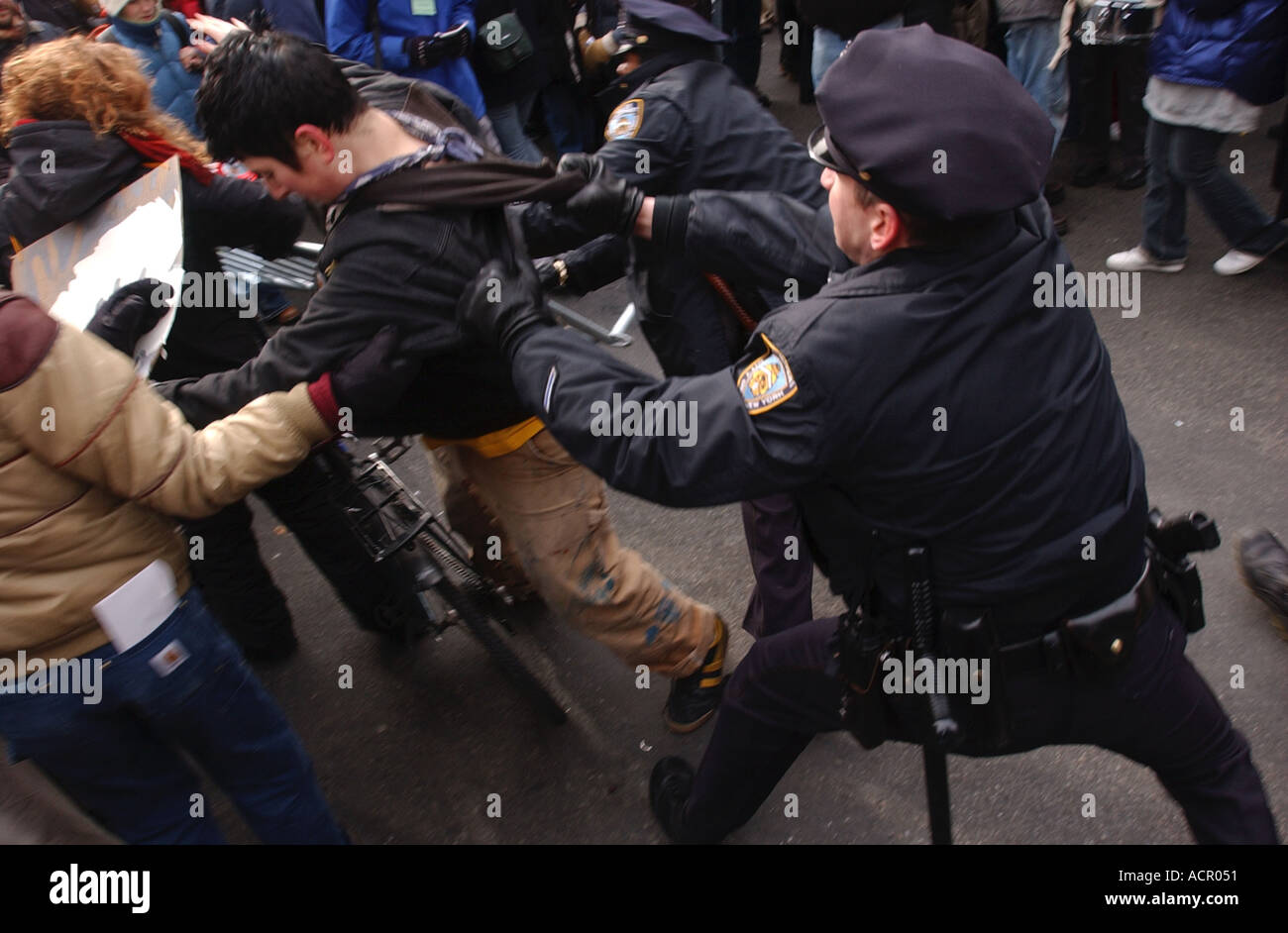 Police officer arresting protester during anti war protests in New York City at start of Iraq War - Stock Image