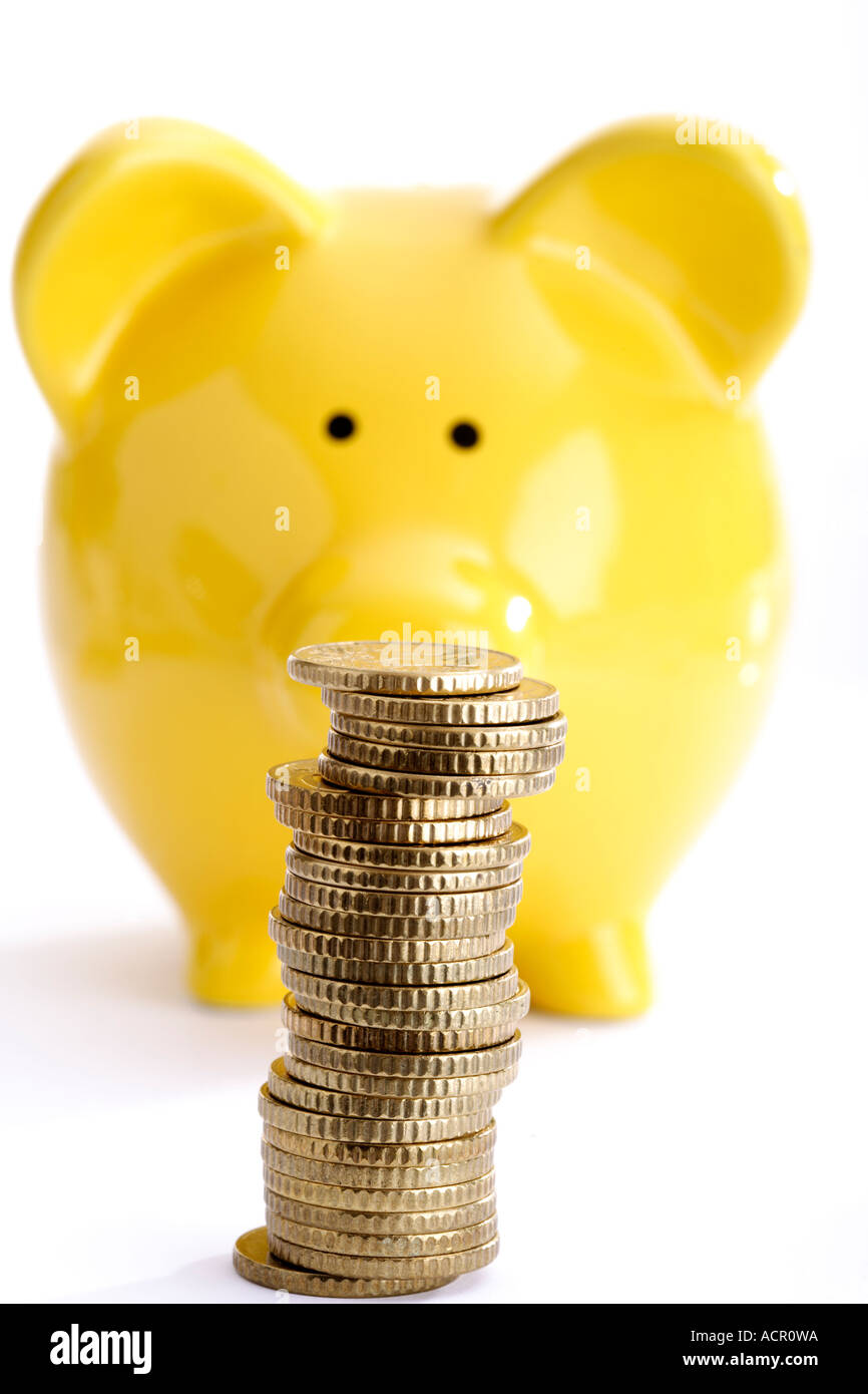 Pile of coins against yellow piggy bank - Stock Image