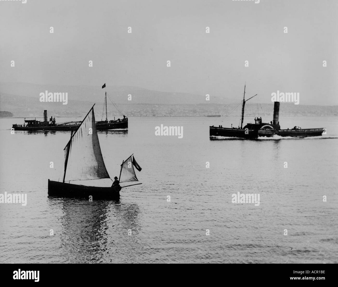 UK Scotland Firth of Clyde in the 1890 s off Greenock sailing boat and paddle tug - Stock Image
