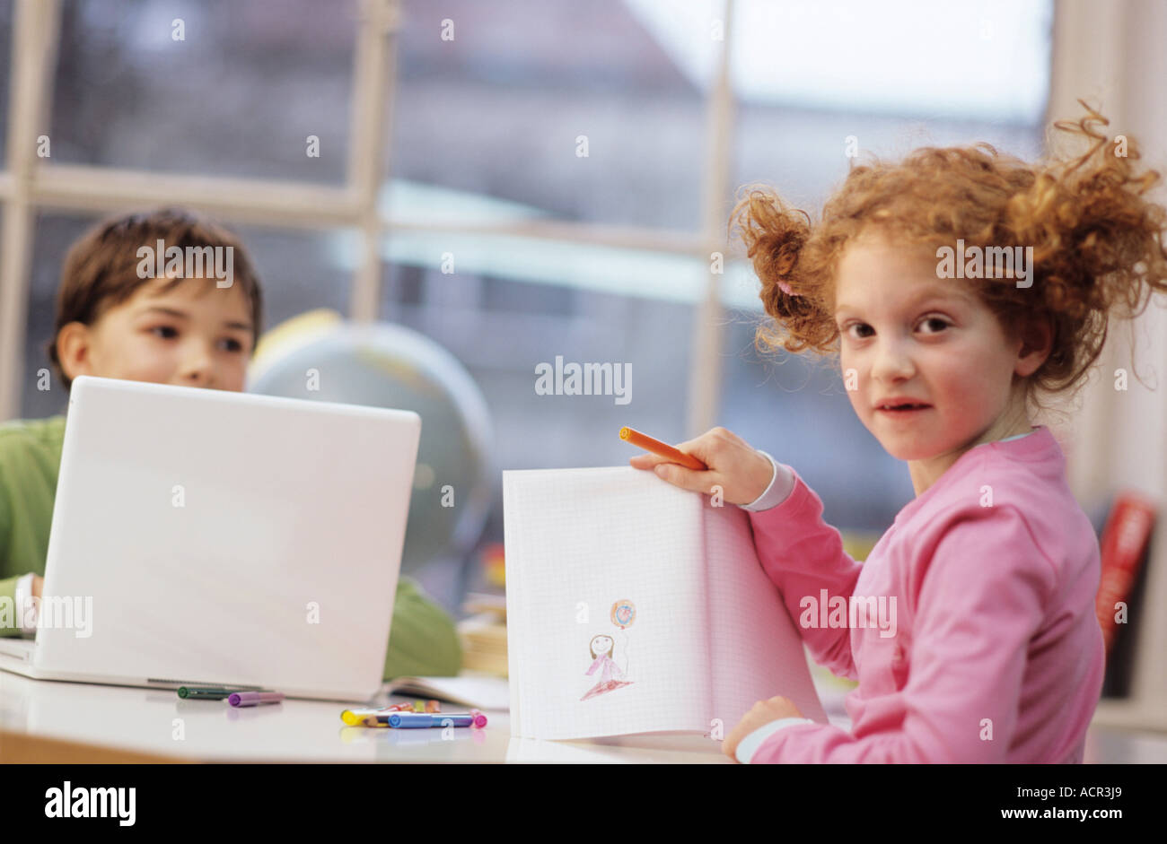 Boy using laptop, girl (7-9) drawing - Stock Image