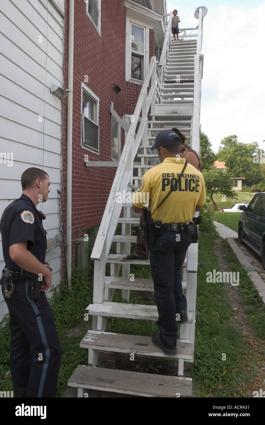The officer in the yellow shirt translates for his colleague and the witness Des Moines PD Iowa - Stock Image