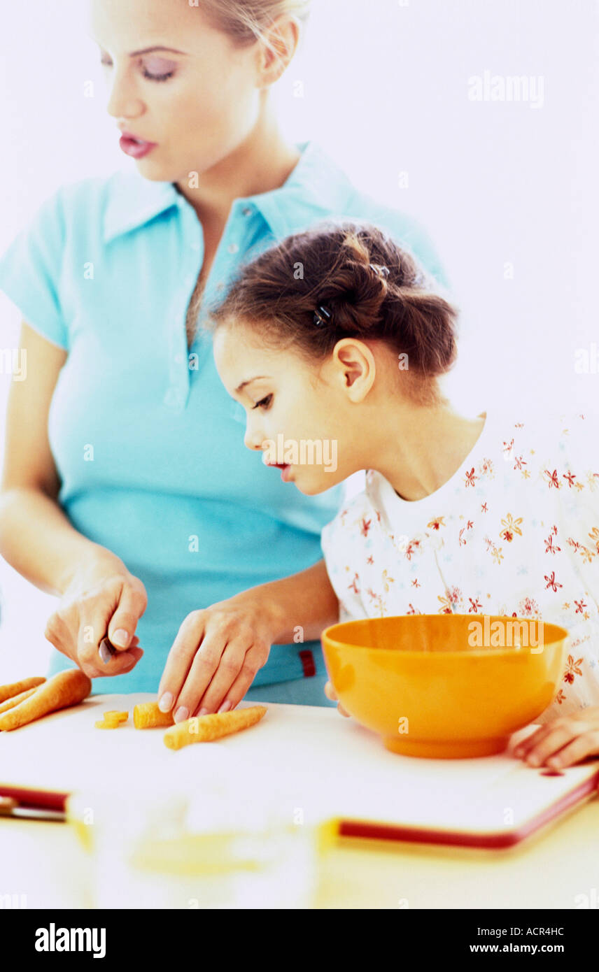 Daughter watching mother cut carrot - Stock Image