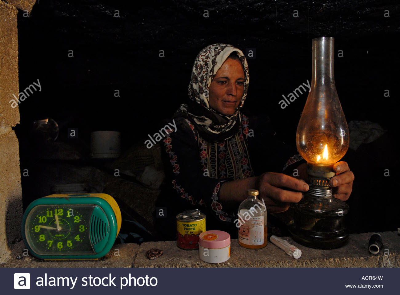 A Palestinian woman lighting a kerosene lamp in an inhabited cave in Al Mufaqarah village located in South Hebron - Stock Image