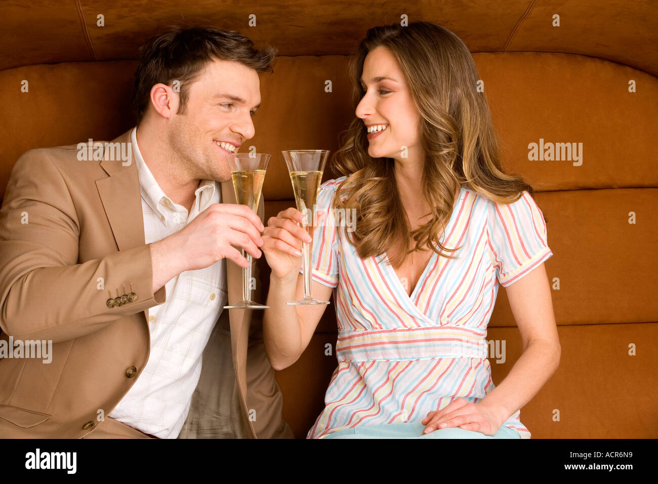 Young couple on sofa holding champagne glasses, smiling - Stock Image