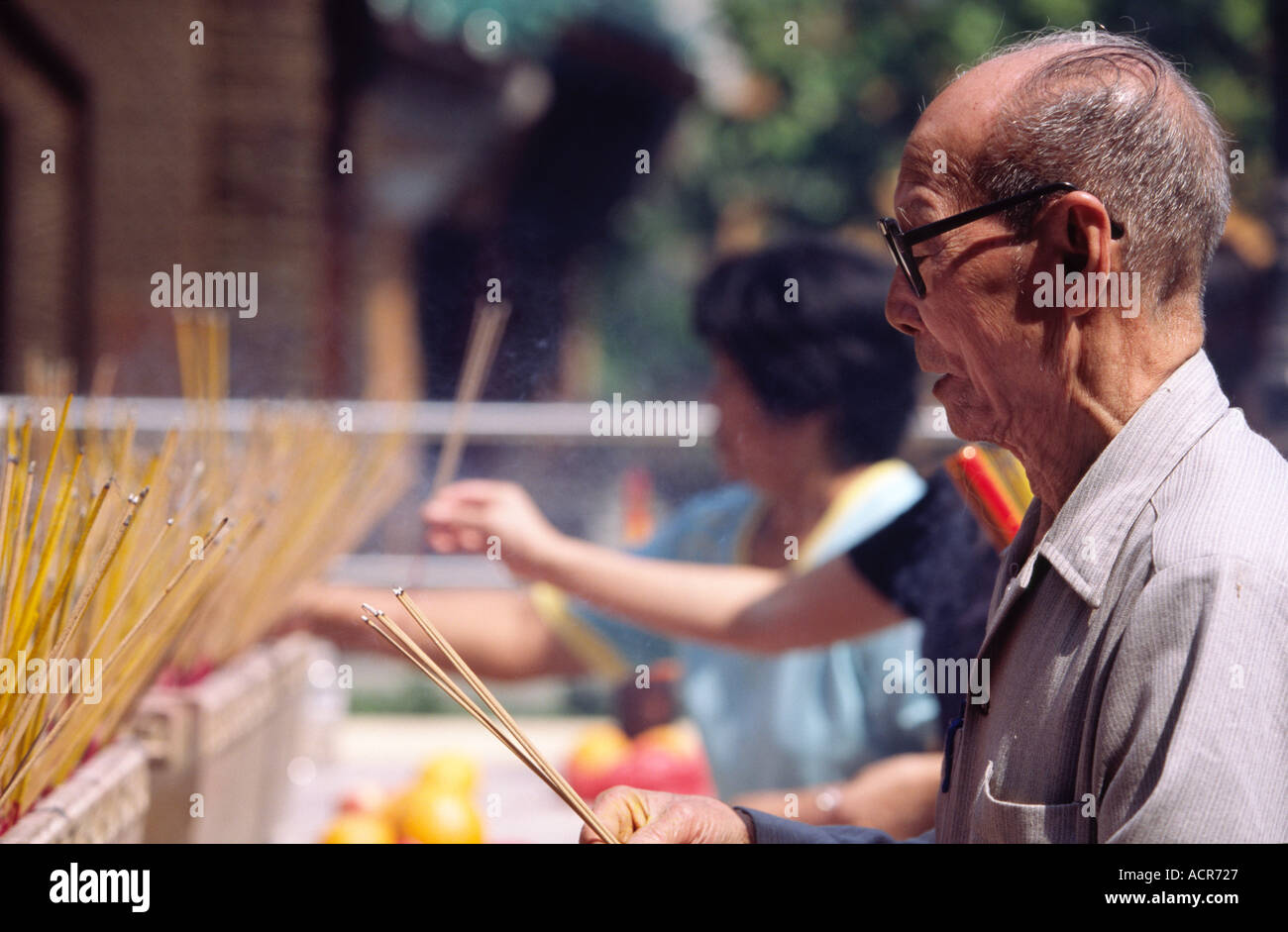 Old man making offering Wong Tai Sin Temple Kowloon Stock Photo