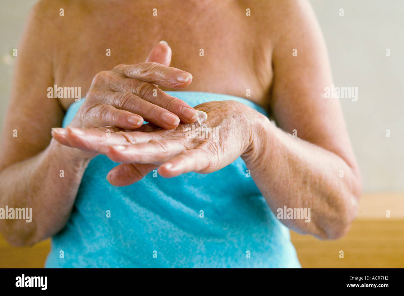 Senior woman wrapped in towel, applying lotion in hands, mid section, close-up - Stock Image