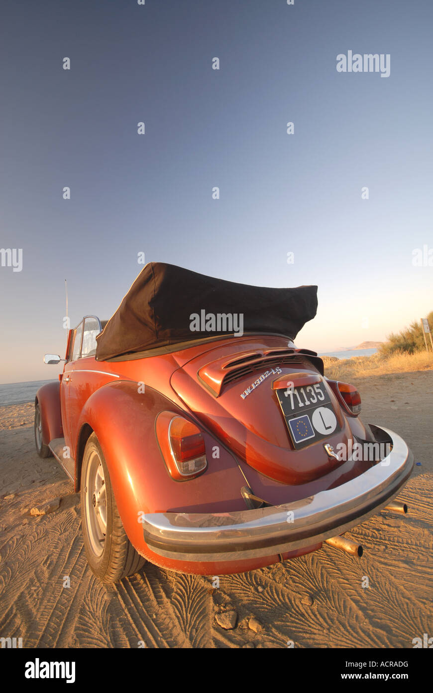 A shiny orange-red convertible Volkswagen Beetle on the beach. 2007. - Stock Image