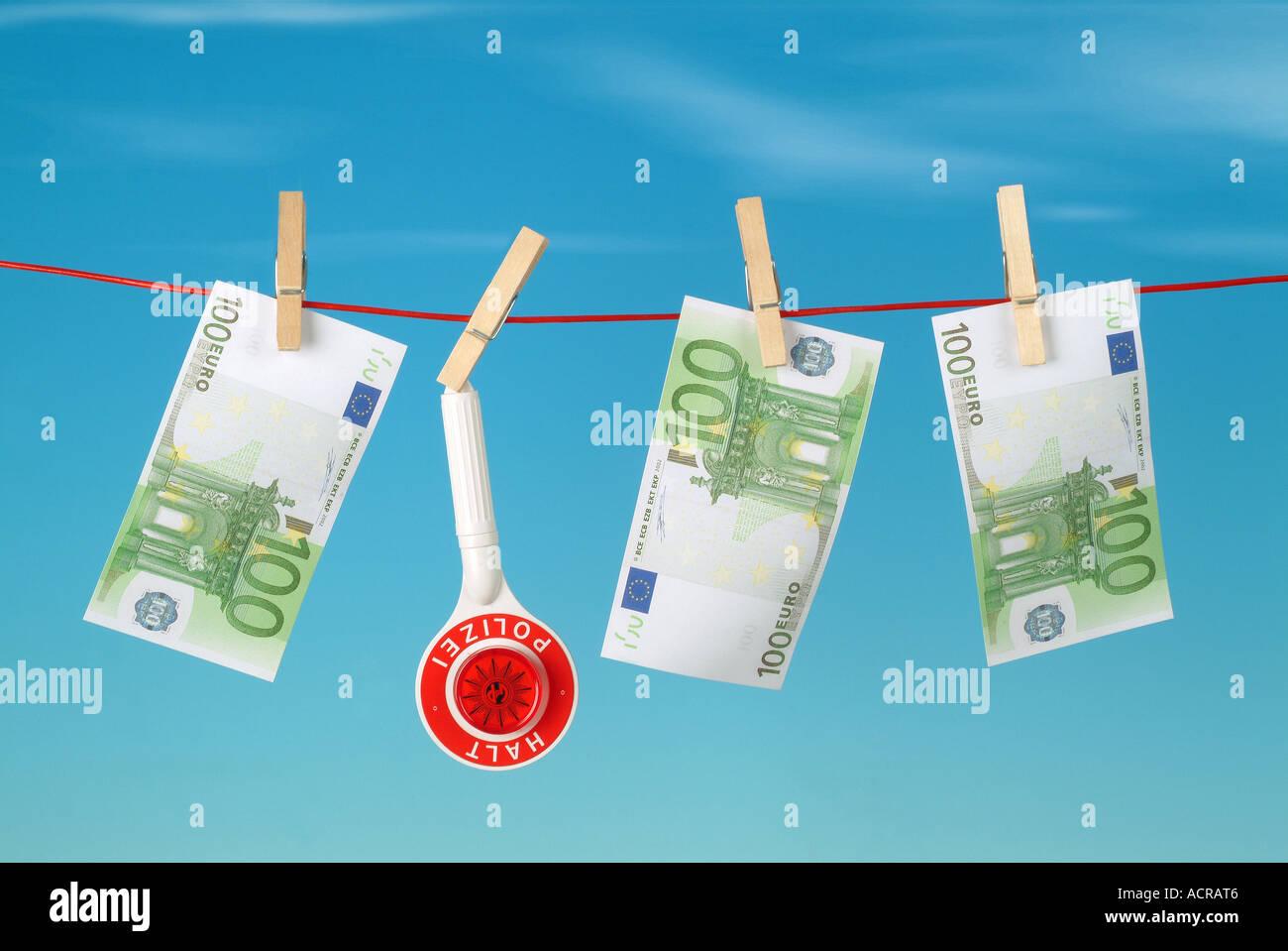 euros on a clothesline Euros und Polizeikelle auf Wäscheleine - Stock Image