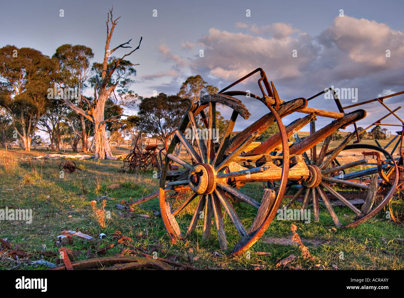 an old cart lays rotting on the farm at sunset - Stock Image