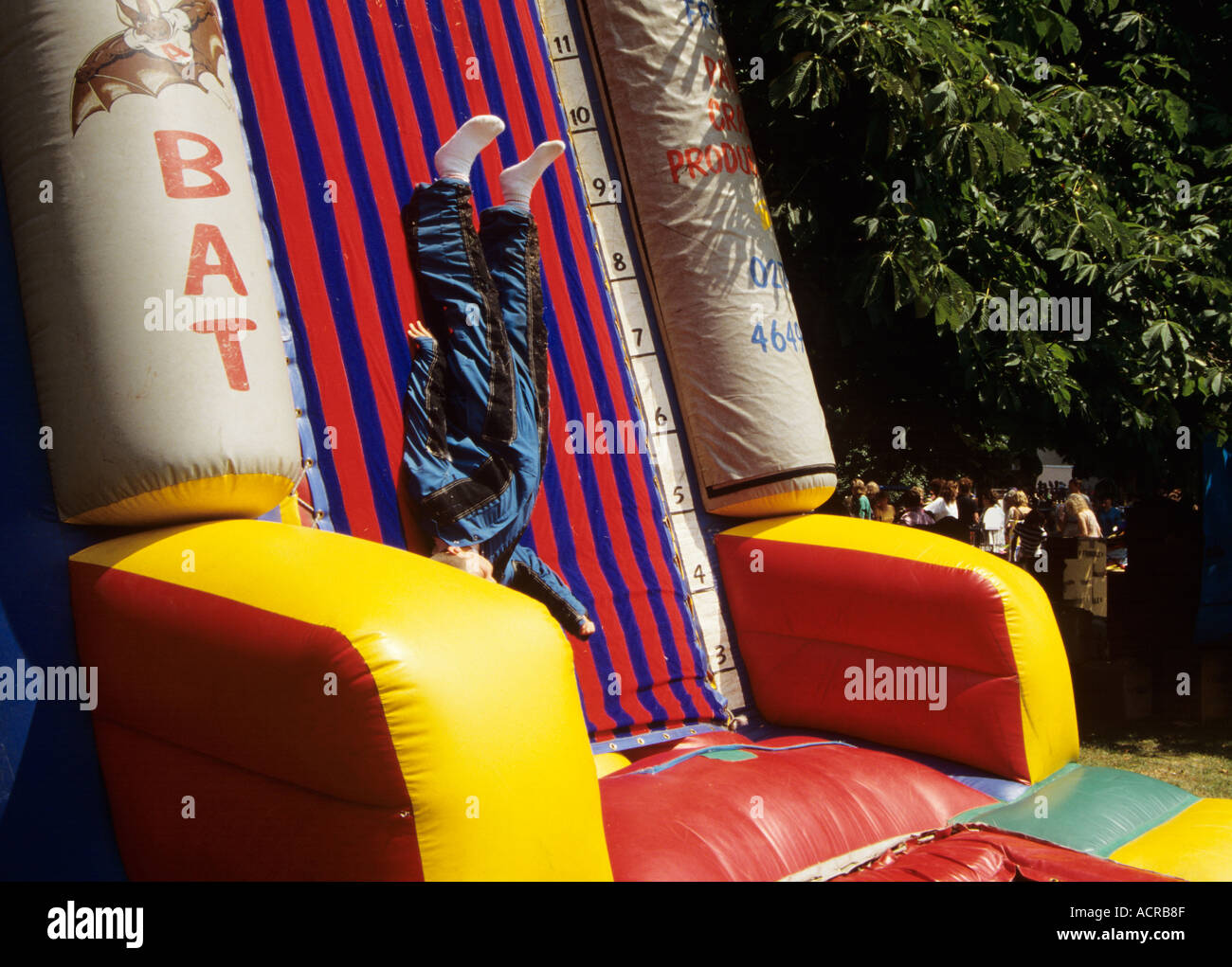 Boy attempting Velcro Wall dressed in special velcro suit at fair in London Stock Photo